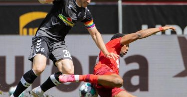 Der Kölner Kingsley Ehizibue (r) geht im Zweikampf mit Christian Günter zu Boden. Foto: Rolf Vennenbernd/dpa
