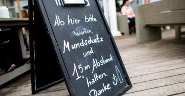 «Mundschutz und 1,5 m Abstand halten» steht auf einem Schild vor einem Lokal auf der Nordseeinsel Norderney. Niedersachsen öffnet den Tourismus zunächst nur für die Einwohner des eigenen Bundeslandes. Foto: Hauke-Christian Dittrich/dpa