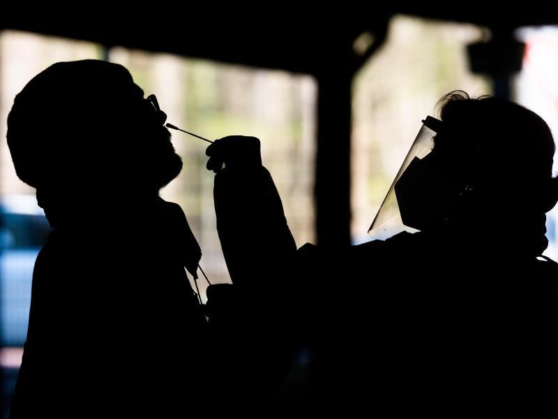 Helfer testen einen Mann im «Testzentrum am Zoo» in Hannover mit einem Schnelltest auf das Coronavirus. Foto: Julian Stratenschulte/dpa