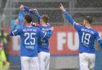 Die Kieler Spieler Phil Neumann (l-r), Hauke Wahl und Simon Lorenz halten nach dem Treffer zum 1:1 ein Trikot des verletzten Mannschaftskameraden Ahmet Arslan hoch. Foto: Frank Molter/dpa
