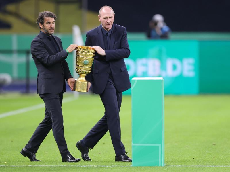 Karl-Heinz Riedle (l) und Perry Bräutigam tragen den DFB-Pokal auf das Feld. Foto: Jan Woitas/dpa-Pool/dpa