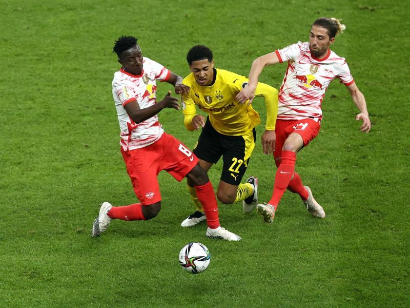Dortmunds Mittelfeldspieler Jude Bellingham (M) wird von Leipzigs Amadou Haidara (l) und Kevin Kampl (r) in die Zange genommen. Foto: Maja Hitij/Getty-Pool/dpa