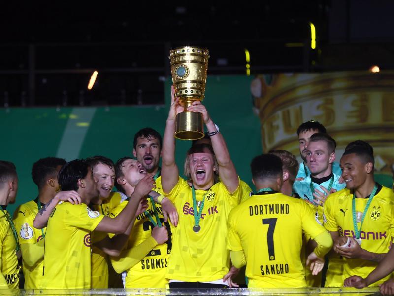 Dortmunds Top-Stürmer Erling Haaland hebt den Pokal in die Höhe. Der BVB hat den DFB-Pokal zum fünften Mal gewonnen. Foto: Martin Rose/Getty-Pool/dpa