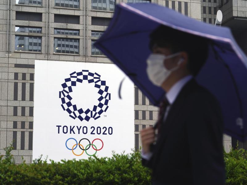 Ein Mann mit Mund-Nasen-Schutzt geht im Regen an einem Banner der Olympischen Spiele Tokio 2020 vorbei. Foto: Eugene Hoshiko/AP/dpa