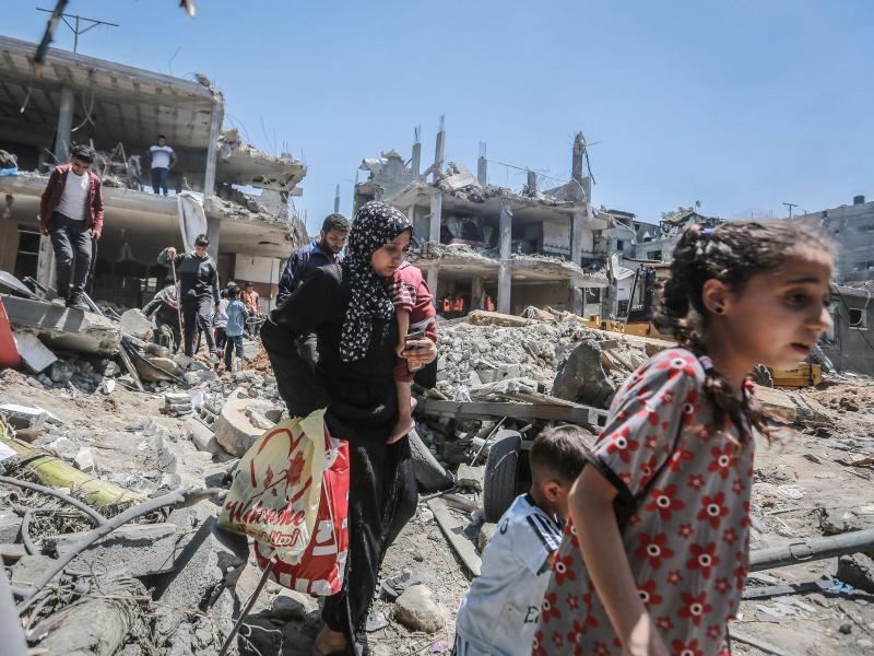 Einwohner vonGaza gehen durch die Trümmer, die ein israelischer Luftangriff hinterlassen hat. Foto: Mohammed Talatene/dpa