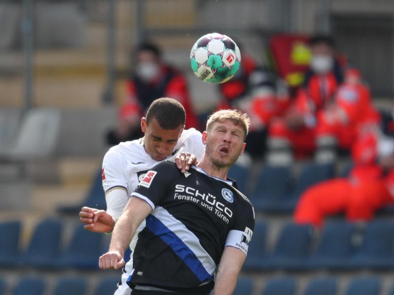Bielefelds Fabian Klos (vorne) im Kopfballduell mit Hoffenheims Kevin Akpoguma. Foto: Friso Gentsch/dpa