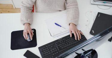 Eine Frau arbeitet in ihrer Wohnung vor einem Computer an einem Stehtisch. (Symbolbild). Foto: Uwe Anspach/dpa