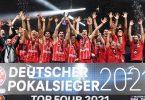 Die Bayern jubeln nach dem Spiel mit der Trophäe. Foto: Tobias Hase/dpa