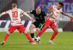 Wolfsburgs Xaver Schlager (M) im Zweikampf mit den Leipzigern Christopher Nkunku (r) und Emil Forsberg. Foto: Michael Sohn/AP-Pool/dpa