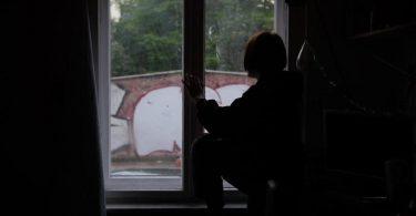 Eine Jugendliche sitzt in einem abgedunkelten Zimmer am Fenster. Foto: Paul Zinken/dpa