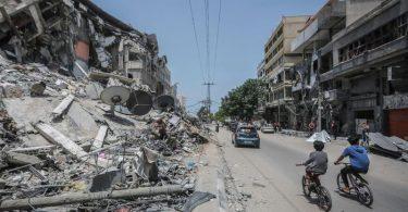 Palästinenser fahren an Gebäuden in Gaza vorbei, die durch israelische Luftangriffe zerstört wurden. Foto: Mohammed Talatene/dpa