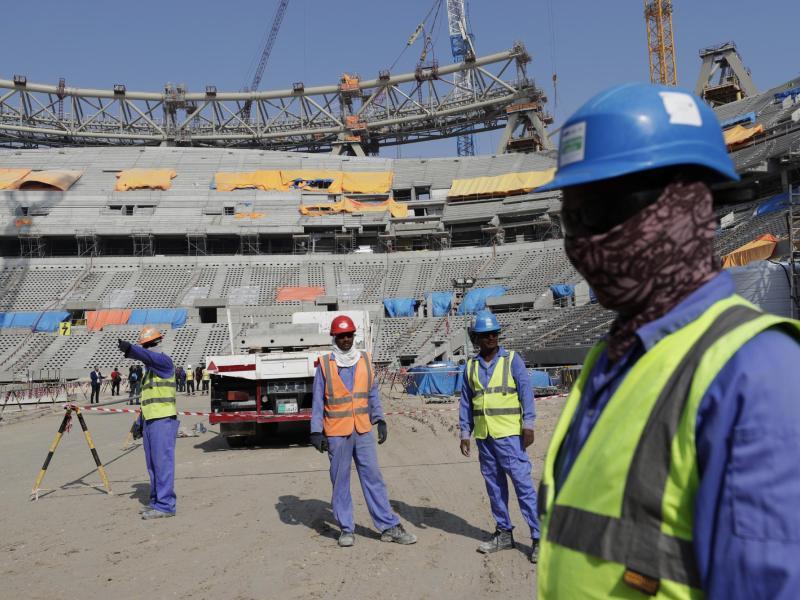 Bauarbeiter arbeiten am Lusail-Stadion, einem der Stadien der WM 2022. Foto: Hassan Ammar/AP/dpa