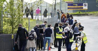 Menschen warten in einer Schlange vor dem mobilen Covid-Impfzentrum an der ESSA-Akademie in Bolton. Foto: Danny Lawson/PA Wire/dpa