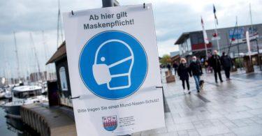 Ein Schild mit der Aufschrift «Ab hier gilt Maskenpflicht» hängt an der Promenade. Foto: Daniel Bockwoldt/dpa