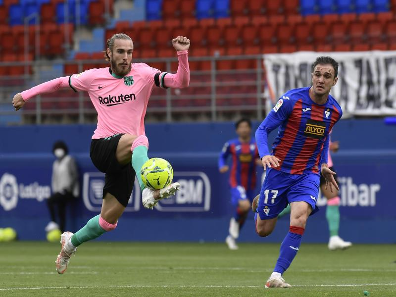 Barcelonas Oscar Mingueza (l) im Laufduell mit Eibars Kike Garcia, der den Ball eng am Fuß führt. Foto: Alvaro Barrientos/AP/dpa