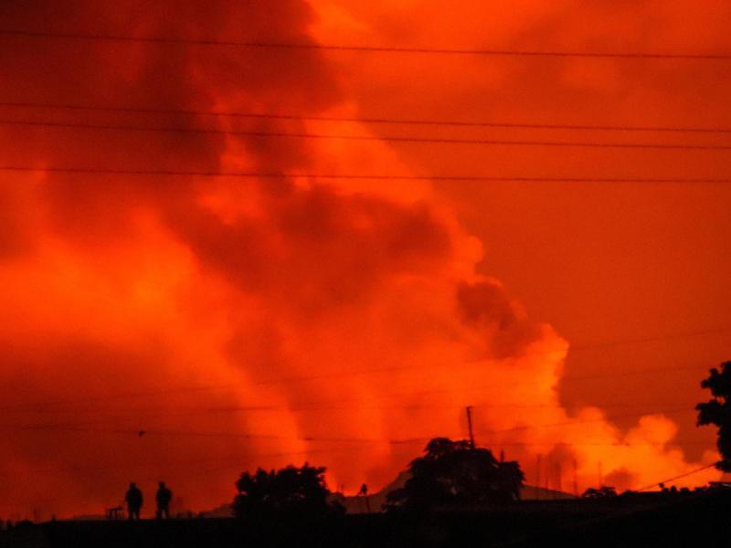 Zwei Menschen sind gegen einen Nachthimmel zu sehen, der einen Vulkanausbruch rot gefärbt ist. Im Osten der Demokratischen Republik Kongo hat ein Ausbruch des Vulkas Mount Nyiragongo Panik in der Bevölkerung ausgelöst. Der aktive Vulkan befindet sich im Virunga-Nationalpark, knapp 20 Kilometer nördlich der Stadt Goma und damit nahe der Grenze zu Ruanda. (zu dpa: «Vulkanausbruch im Osten Kongos löst Panik aus»). Foto: Justin Kabumba/AP/dpa