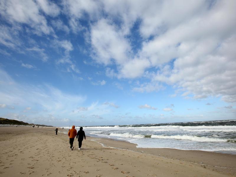 Bei windigem Wetter sind Spaziergänger am Strand von Westerland auf Sylt unterwegs. Foto: Bodo Marks/dpa