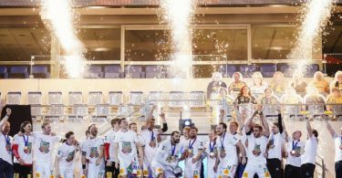 Magdeburgs Mannschaft feiert mit dem Siegerpokal den Finalsieg über die Füchse Berlin. Foto: Uwe Anspach/dpa