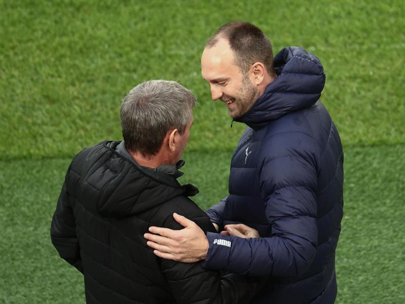 Kiels Trainer Ole Werner (r) begrüßt Kölns Trainer Friedhelm Funkel. Foto: Rolf Vennenbernd/dpa Pool/dpa