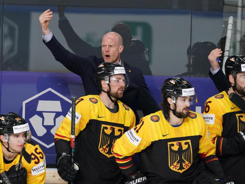 Trainer Toni Söderholm (hinten, links) und das DEB-Team sind gegen die USA gefordert. Foto: Roman Koksarov/dpa