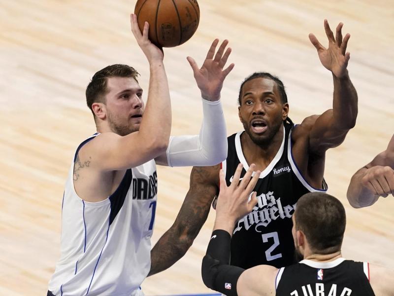 Luka Doncic (l) von den Dallas Mavericks wirft, während Kawhi Leonard (2) und Ivica Zubac von den Los Angeles Clippers verteidigen. Foto: Tony Gutierrez/AP/dpa