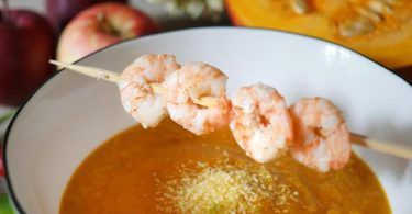 Einen Hauch Exotik bekommt die Kürbissuppe durch Kokosraspeln und Limette. Perfekte Ergänzung dazu sind die gebratenen Garnelen. Foto: Doreen Hassek/dekoreenberlin.blogspot.com/dpa-tmn