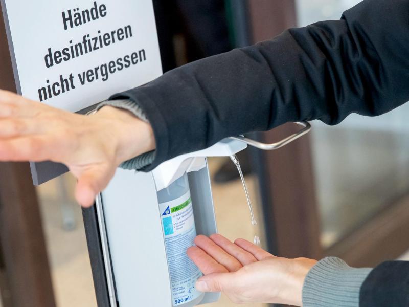 Spender mit Desinfektionsmittel stehen vor vielen Eingängen, unter anderem von Behörden und Geschäften. Foto: Daniel Karmann/dpa/dpa-tmn
