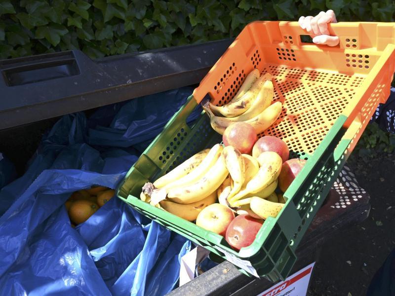 Ein Mitarbeiter eines Supermarktes bringt Obst zu einem Müllcontainer. (Symbolbild). Foto: Carmen Jaspersen/dpa