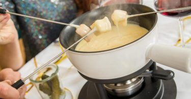 Ein Schuss Wein sorgt beim Käsefondue für die richtige Konsistenz. Foto: Christin Klose/dpa-tmn