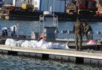 Einsatzkräfte der tunesischen Küstenwache im Hafen von Sfax neben zugedeckten Leichen auf einem Steg. Foto: Houssem Zouari/AP/dpa