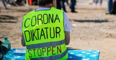 Ein Teilnehmer trägt auf dem Cannstatter Wasen bei einer Kundgebung der Initiative «Querdenken 711» eine Warnweste mit der Aufschrift «Corona Diktatur stoppen». Foto: Christoph Schmidt/dpa