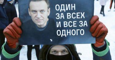 «Einer für alle und alle für einen»:Ein Demonstrant in St. Petersburg mit einem Plakat, auf dem das Konterfei von Alexej Nawalny zu sehen ist. Foto: Dmitri Lovetsky/AP/dpa