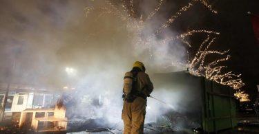 Krawalle inRotterdam:Ein Feuerwehrmann löscht einen Container, der bei Protesten gegen die landesweite Ausgangssperre in Brand gesetzt wurde. Foto: Peter Dejong/AP/dpa