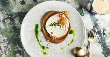 Das Dessert aus dem Restaurant Coda ist eine Kombination aus schwarzem Knoblauch und Petersilienwurzeleis. Durch die Karamellisierung entwickelt der Knoblauch Aromen in Richtung Kakao, Kaffee und Balsamico. Das Eis wird mit entsafteter Petersilienwurzel, Kokosmilch und Honig zubereitet. Foto: JUNI/dpa-tmn