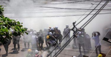 Demonstranten tragen in Rangun in einer Wolke von Tränengas Schutzhelme, um sich gegen die Gewalt zu schützen. Foto: Aung Kyaw Htet/SOPA Images via ZUMA Wire/dpa