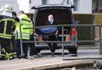 Mitarbeiter eines Bestattungsunternehmens tragen ein Opfer zu einem Leichenwagen. Foto: Jan Woitas/dpa-Zentralbild/dpa