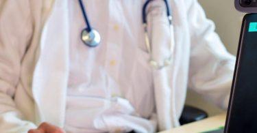 Ein Hausarzt sitzt während einer Videosprechstunde in seiner Praxis vor einem Laptop. Foto: Monika Skolimowska/dpa-Zentralbild/ZB