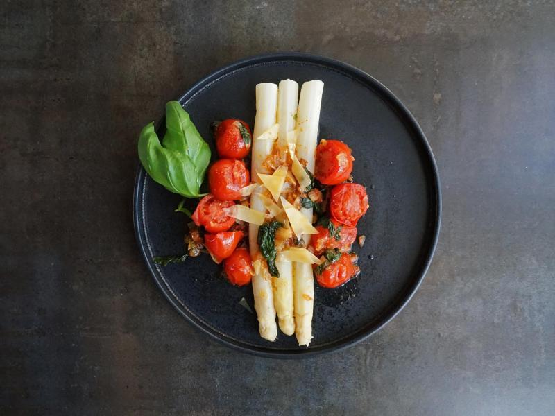 Mal ohne die Klassiker Kartoffeln und Schinken: Auch Tomaten, Zwiebeln und Basilikum passen zu weißem Spargel. Foto: Manfred Zimmer/herrgruenkocht.de/dpa-tmn
