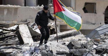 Ein Polizist der Hamas entfernt eine palästinensische Fahne von einem Trümmerhaufen eines Bahnhofsgebäudes, das bei Luftangriffen zerstört worden war. Foto: John Minchillo/AP/dpa