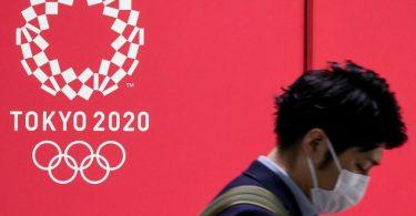 Von Euphorie ist in Japan vor den Sommerspielen wenig zu spüren: Ein Mann mit Mund-Nasen-Schutz geht an einem Werbeplakat vorbei. Foto: Cezary Kowalski/SOPA Images via ZUMA Wire/dpa
