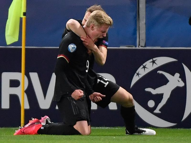 Torschütze Jonathan Burkardt und Teamkollege Paul Jaeckel (hinten) feiern das 1:2 gegenDänemark. Foto: Marton Monus/dpa