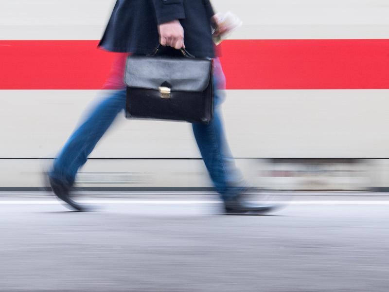 Ein Bahnpendler mit Aktenkoffer geht an einem Zug vorbei. Ein Jahr nach der Einigung der schwarz-roten Koalition auf ein milliardenschweres Konjunkturpaket gegen die Auswirkungen der Corona-Krise fordern Wirtschaft und Gewerkschaften zusätzliche Reformen. Foto: Sebastian Gollnow/dpa