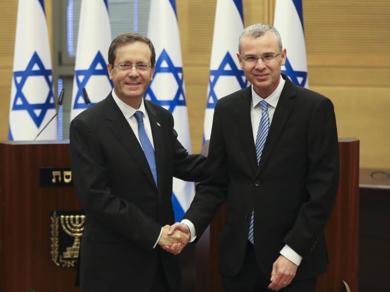 Izchak Herzog (l) gibt Knesset-Präsident Jariv Levin vor einer Sondersitzung die Hand. Israels Parlament hat den früheren Oppositionsführer zum Staatspräsidenten gewählt. Foto: Ronen Zvulun/Pool Reuters/AP/dpa