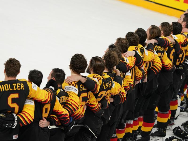 Das deutsche Eishockey-Nationalteam steht Arm in Arm auf dem Eis. Foto: Roman Koksarov/dpa