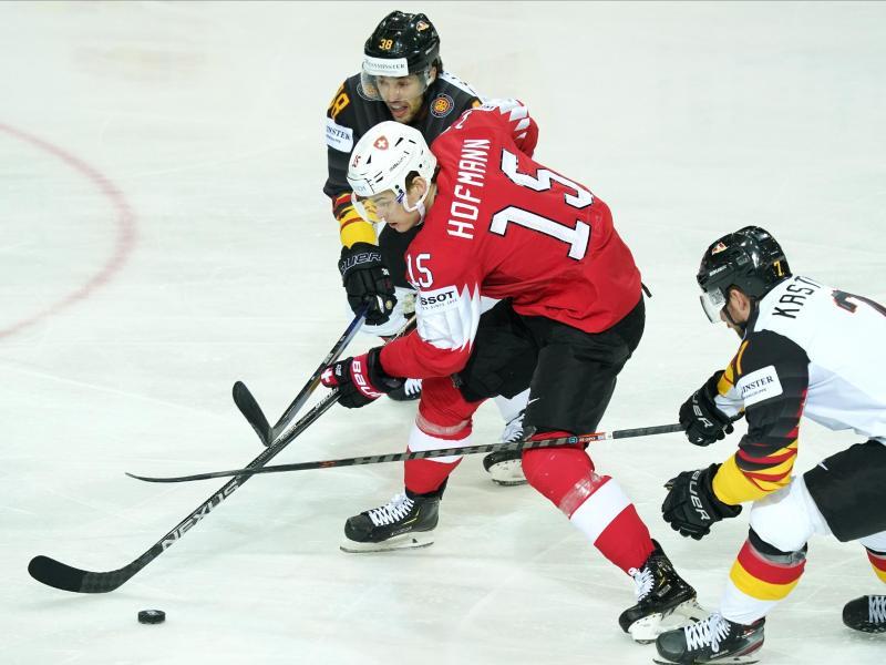 Fabio Wagner (l) und Maximilian Kastner (r) attackieren den Schweizer Gregory Hofmann. Foto: Roman Koksarov/dpa