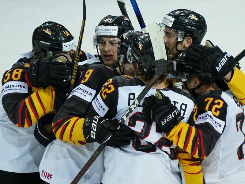 Die deutsche Eishockey-Nationalmannschaft feiert den Einzug ins Halbfinale. Foto: Roman Koksarov/dpa