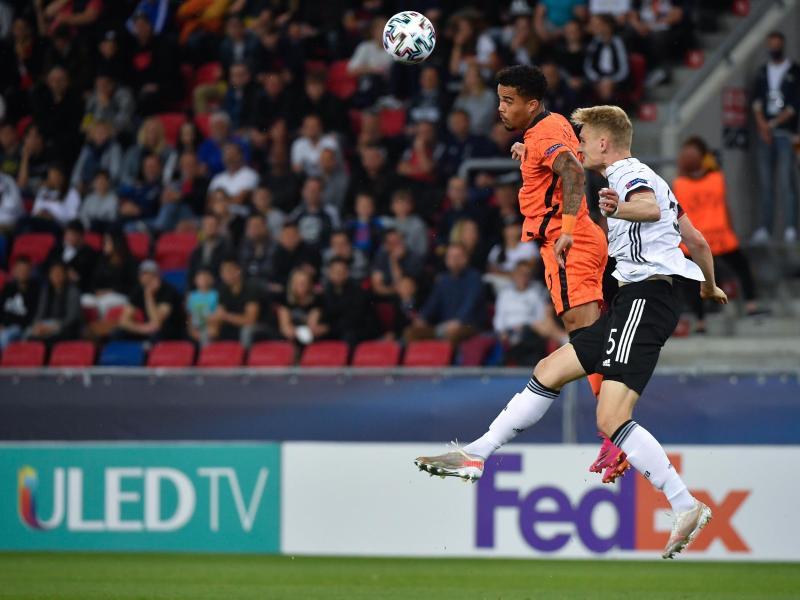 Amos Pieper (r) kämpft mit dem Niederländer Justin Kluivert um den Ball. Foto: Marton Monus/dpa