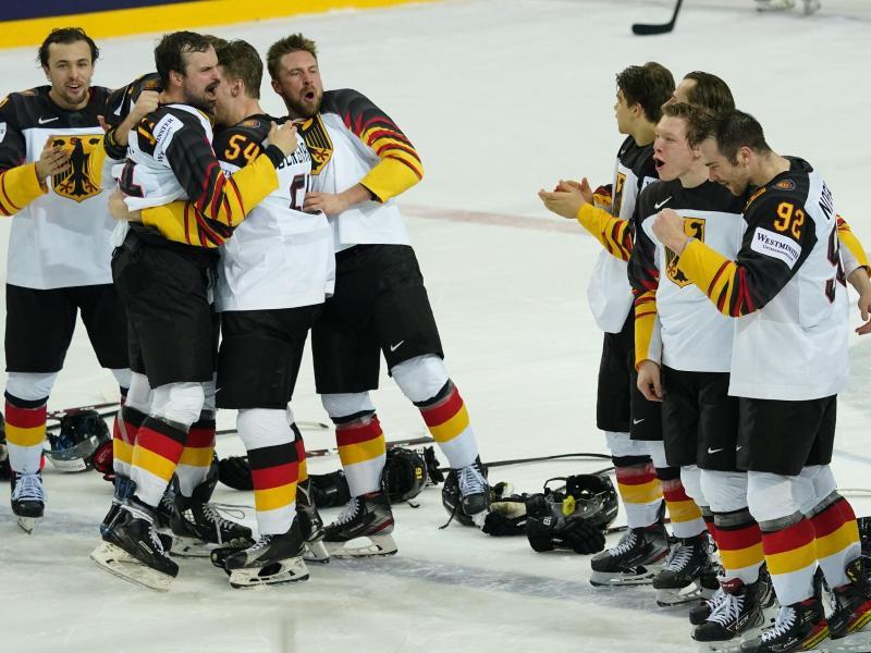 Die deutschen Nationalspieler feiern ihren Erfolg auf dem Eis. Foto: Roman Koksarov/dpa