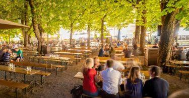 Besucher sitzen im Biergarten: Bayern überlegt auch Innen wieder zu öffnen. Foto: Peter Kneffel/dpa