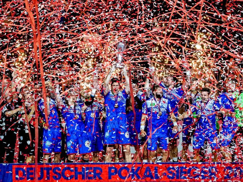 Die Spieler vom TBV Lemgo feiern den Sieg. Foto: Axel Heimken/dpa